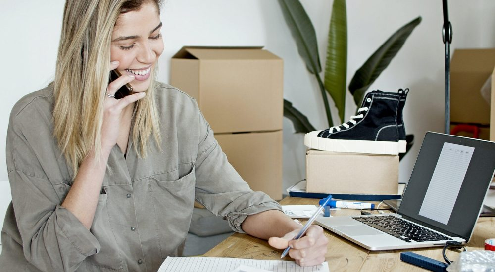 woman on phone call holding pen next to paper